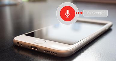"""Imagem: Celular em cima da mesa com um balão de conversa e as palavras """"ok Google"""".dispositivos de voz."""