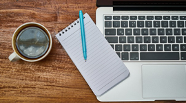 Imagem: notebook com uma xícara de café e bloco de notas.