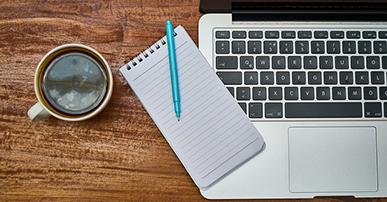 Imagem: notebook com uma xícara de café e bloco de notas. Cursos.