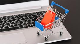 Imagem: mini carrinho de compras com sacolas dentro em cima de um notebook. Representação de e-commerce.