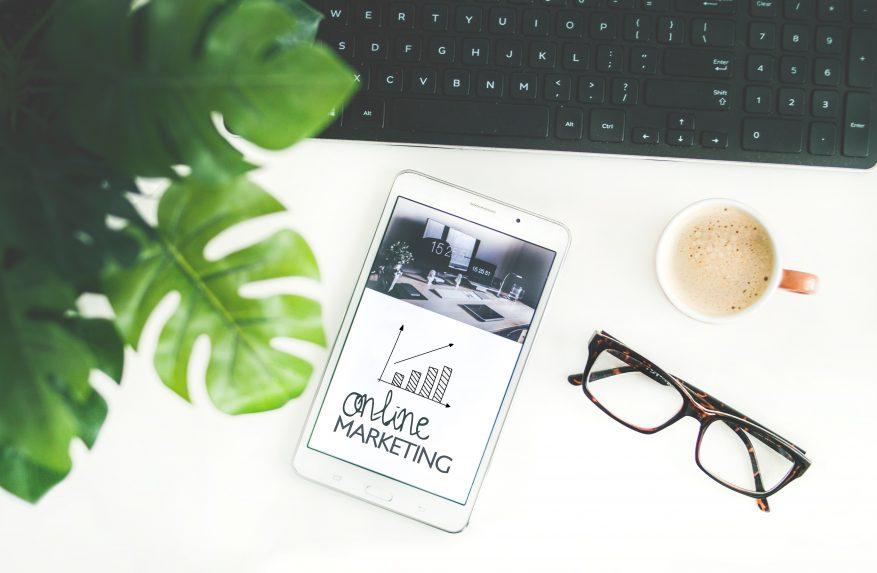 Imagem: celular em cima de uma mesa com teclado, óculos de grau e planta. e-commerce mobile
