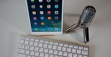 Imagem: tablet com teclado e microfone em cima da mesa. Podcast.