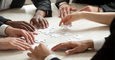 Imagem: grupo de pessoas montando um quebra-cabeça. líder liderança