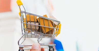 Imagem: Mão segurando uma miniatura de carrinho de compras com caixinhas. Consumidores.