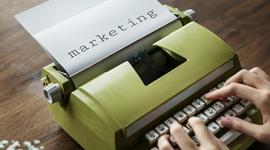"""Imagem: mão escrevendo em máquina de escrever, no papel a palavra """"marketing"""". ferramentas de marketing."""
