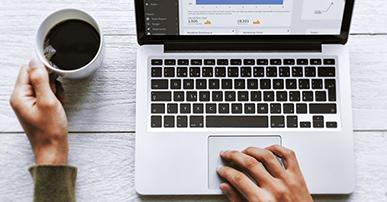 Imagem: mãos segurando uma xícara de café e notebook. redes sociais.