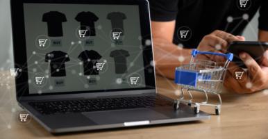 Imagem: mini carrinho de compras ao lado de um notebook, representando compra online.