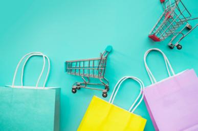 Imagem: sacolas de compras e miniaturas de carrinhos em um fundo azul claro. consumidores.
