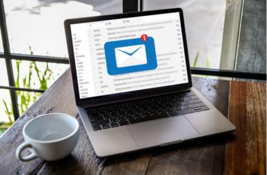 Imagem: Computador em cima da mesa com notificação de e-mail e xícara de café ao lado.