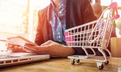 Imagem: pessoa mexendo no computador com um mini carrinho de compras ao lado. estratégias de marketing.