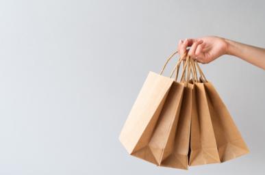 Imagem: fundo cinza com mão segurando sacolas de papel. ciclo de vendas..