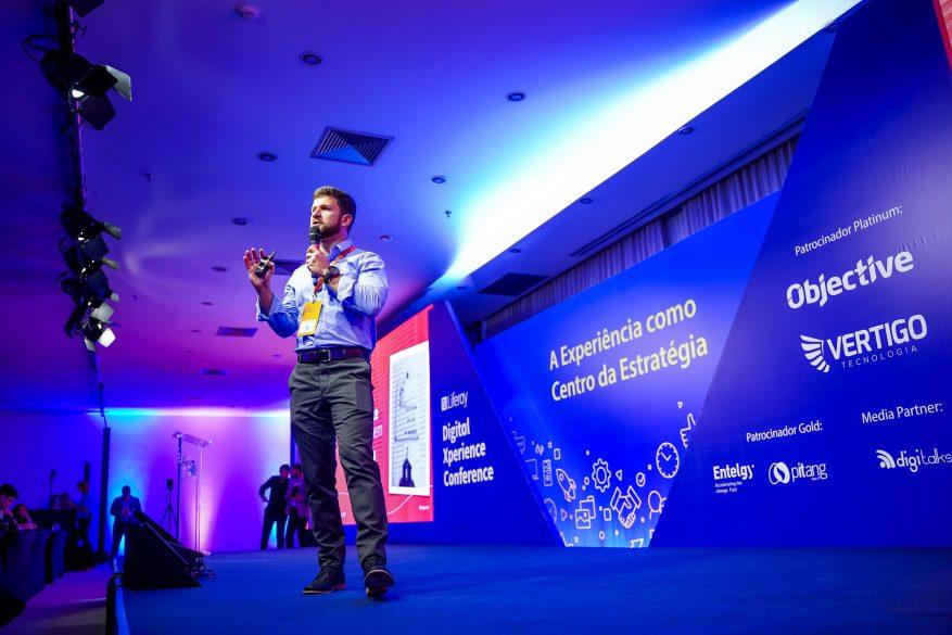 Foto: homem com microfone dando uma palestra sobre experiência.