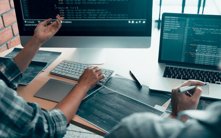 Imagem: dois homens na frente de computadores. informações.