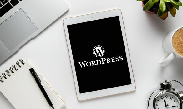Imagem: tablet em cima de uma mesa branca, com o logo do WordPress no visor.