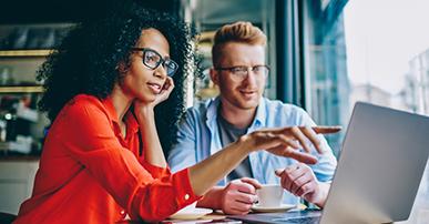 Imagem: homem e mulher sentados à mesa apontando para notebook. Automação de Marketing.