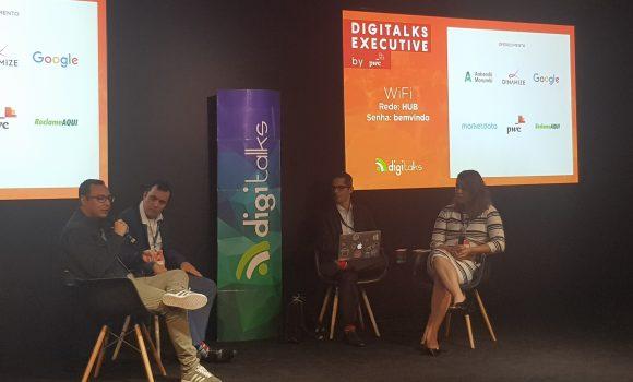 Imagem: 4 pessoas sentadas em cadeiras no palco. Digitalks Executive.