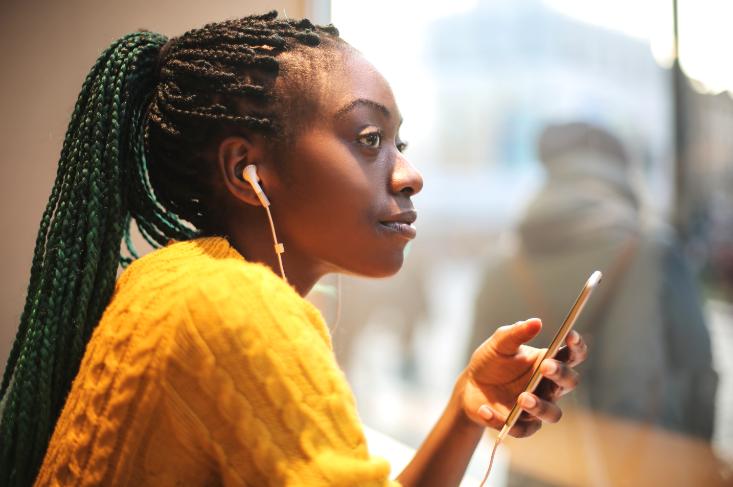 Imagem: moça segurando celular com fones de ouvido. Tecnologias.
