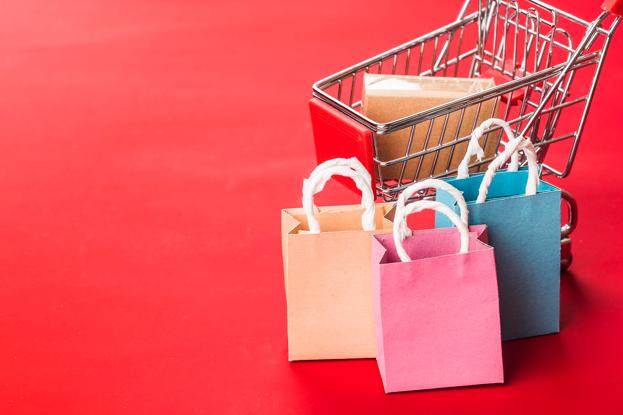 Imagem: fundo vermelho com mini carrinho de compras e sacolas. marketing digital.