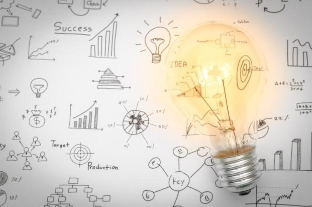 Imagem: lâmpada acessa em cima de um papel com desenhos. gamificação.