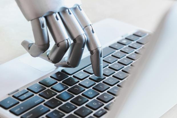 Imagem: mão metálica clicando em tecla de um notebook, representando chatbots.