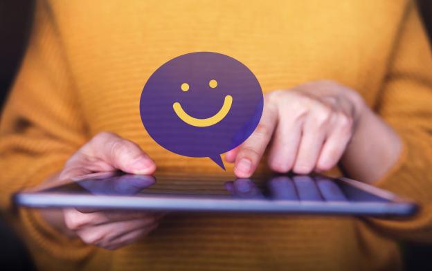 Imagem: pessoa segurando um tablet, com um balão roxo e uma carinha feliz, representando uma boa experiência digital.