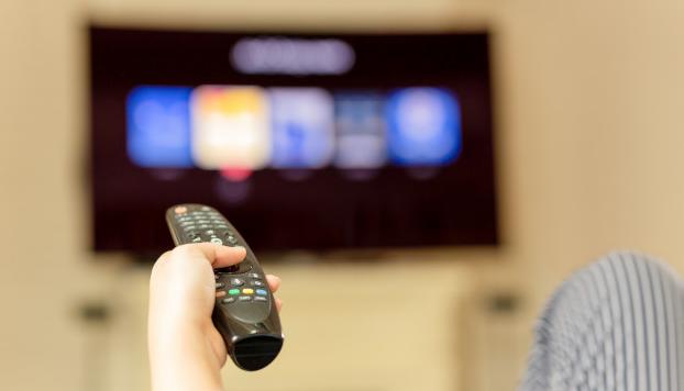 Mão usando o controle remoto para assistir televisão em casa