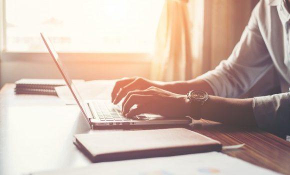 close up das maos masculinas usando laptop em casa
