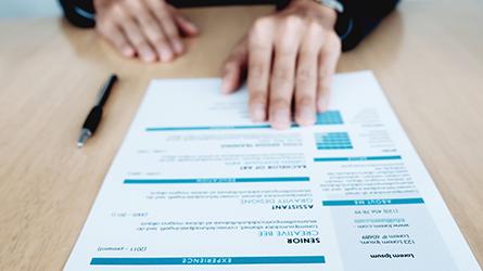 mãos apoiada em um currículo impresso sob uma mesa - mercado de trabalho