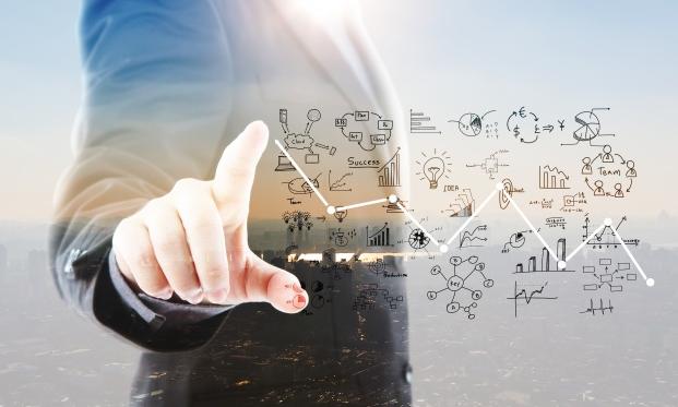 Empresário ponta gráficos e símbolos como futuro.