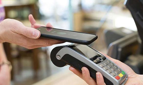 Foto. Na imagem aparecem duas mãos. Um segura um celular e a outra uma máquina de pagamentos para cartão. O celular está próximo da máquina, indicando que está sendo feito um pagamento digital via celular direto para a máquina.