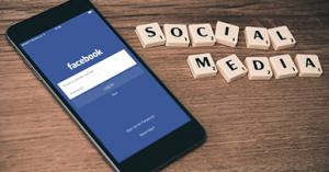 """Imagem: Smartphone na tela inicial do Facebook com peças de jogo ao lado formando a frase """"social media"""". GlobalCoin."""