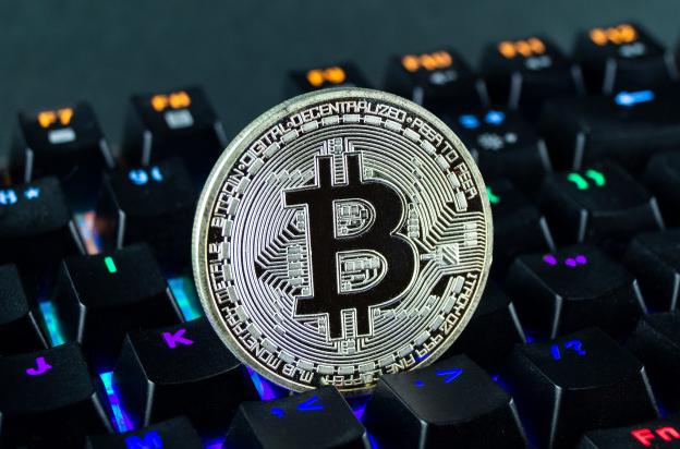 Moeda bitcoin em cima de um teclado de computador.